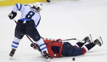 Winnipeg Jets defenseman Jacob Trouba (8) battles for the puck against Washington Capitals defenseman Dmitry Orlov (9), of Russia, during the third period of an NHL hockey game, Sunday, March 10, 2019, in Washington. The Capitals won 3-1. (AP Photo/Nick Wass)