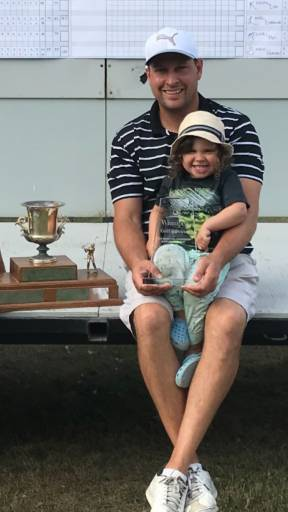 Golfer Brian Melville and his son Mackenzie pose with the Grand Final trophy he captured following a five hole playoff at Windsor Par in 2018. Supplied Photo