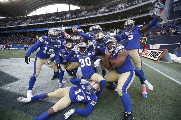 Winnipeg Blue Bombers' Nick Taylor (25), holding ball, and teammates celebrate his interception and touchdown during the second half of CFL action against the Montreal Alouettes, in Winnipeg, Saturday, Oct. 12, 2019.