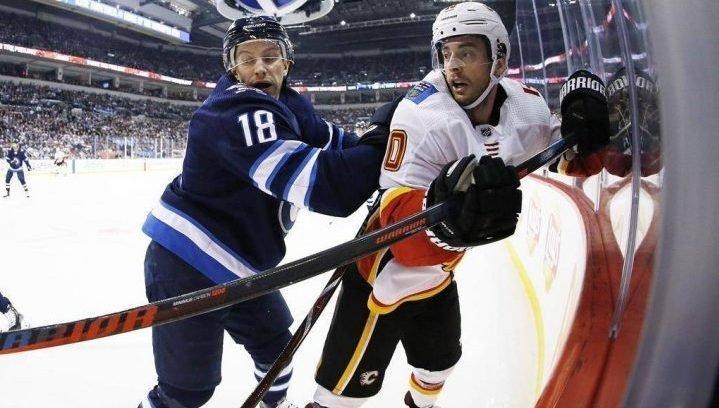 Winnipeg Jets' Bryan Little (18) checks Calgary Flames' Derek Ryan (10) during first period NHL action in Winnipeg on Thursday, Dec. 27, 2018.